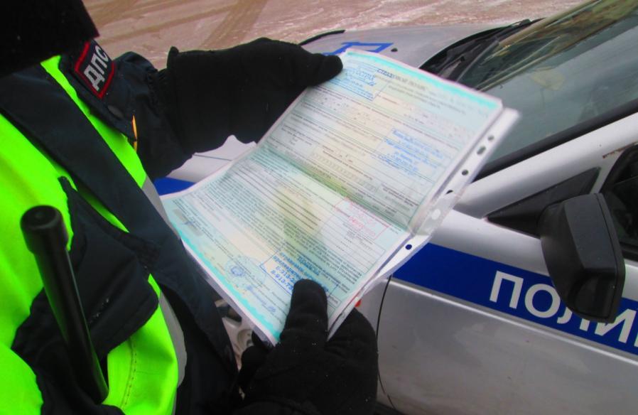 Инспектор ГИБДД проверяет полис ОСАГО